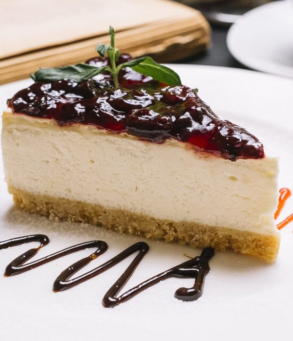 side view of cheesecake with cherry jelly on the top on a white plate